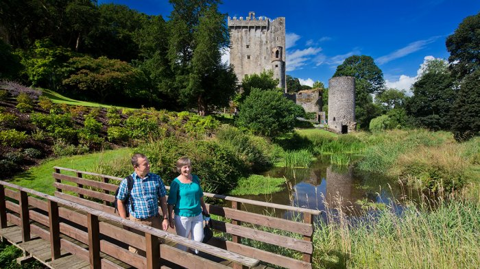 A couple walking across the bridge in Blarney Gardens with Blarney Castle in the background