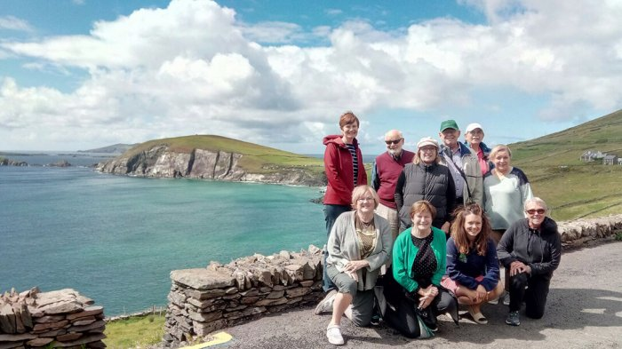 A group of guests posing on Slea Head in the sunshine overlooking the sea
