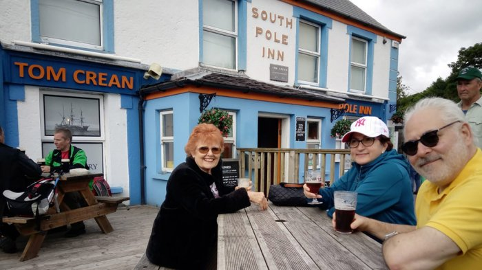 Three people sitting outside the South Pole Inn enjoying a pint