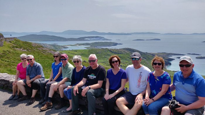 A group of guests sitting on a wall overlooking the Ring of Kerry