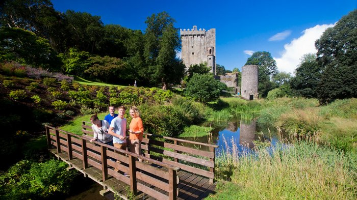 Two women and two men crossing the bridge in Blarney Gardens with Blarney Castle in the background
