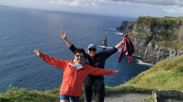 Two women with their hands in the air laughing with the Cliffs of Moher in the background