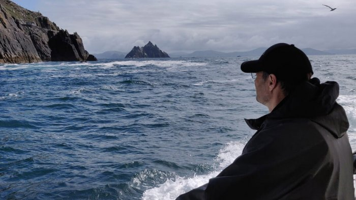 A man on the Skellig Island cruise looking from the boat at Skellig Michael