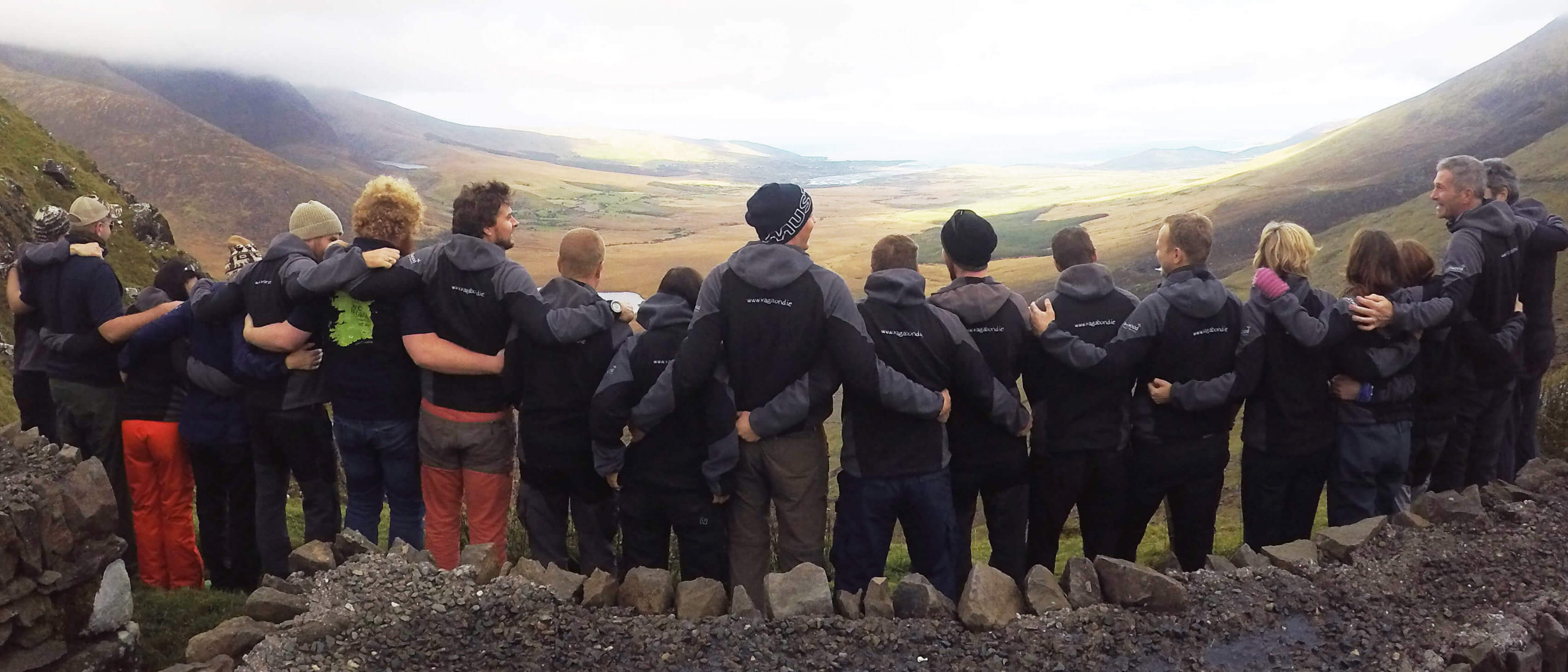 Vagabond tour guides standing on a mountain with their backs to camera