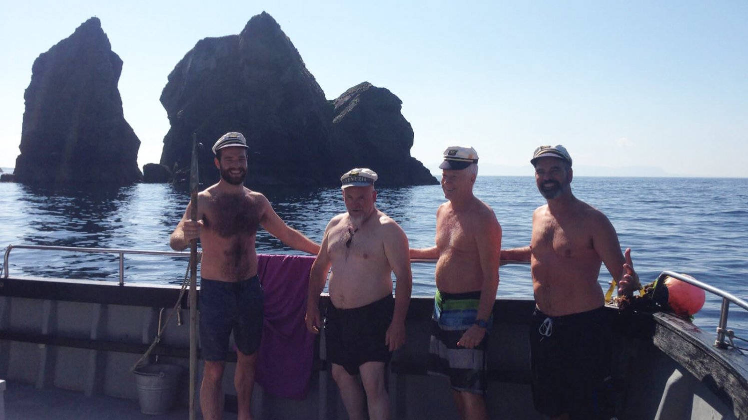 Four men in swimsuits on a boat beside an island