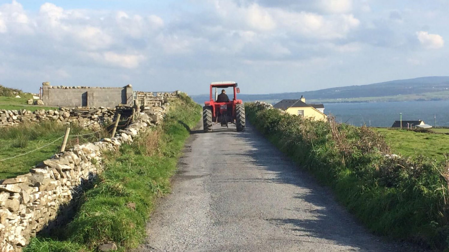 An empty, rural Irish laneway with a dry stone wall and red tractor driving into the distance