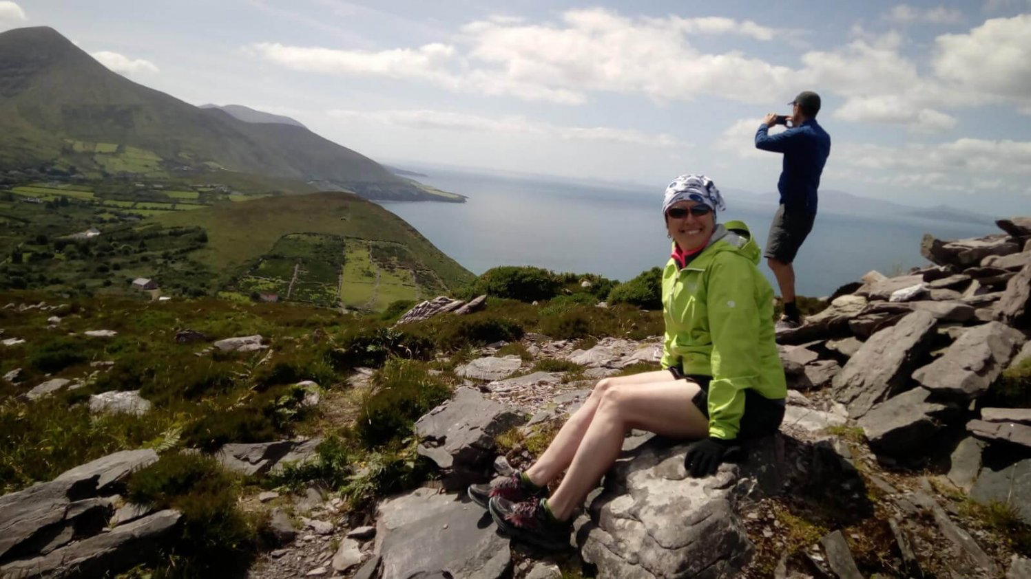 Female hiker and Vagabond tour guest smiles for the camera at the summit of Rossbeigh on the Iveragh peninsula in Kerry, Ireland