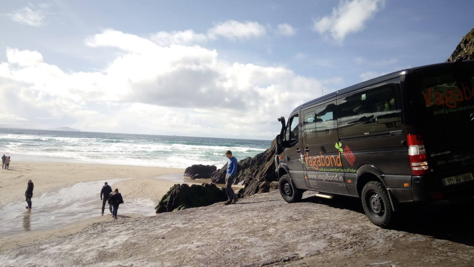 A Vagatron tour vehicle drives onto a beach in Ireland with guests in the background