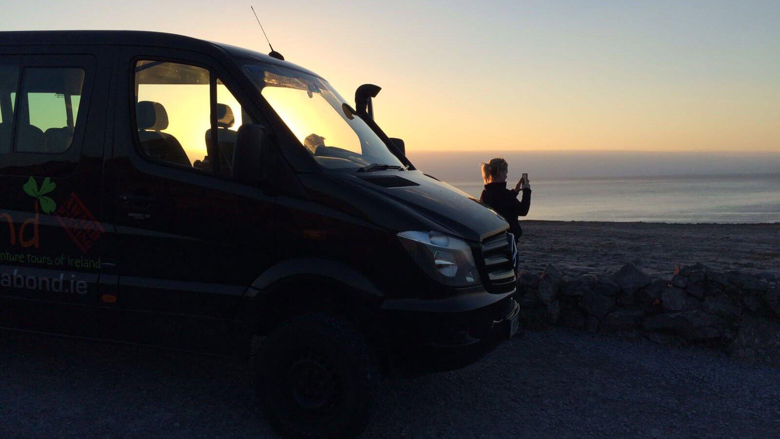 Vagatron tour vehicle with Vagabond tour guide, silhouette by the sun