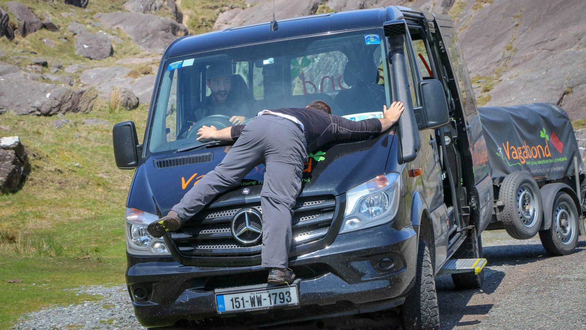 A Vagabond tour guide on the bonnet of Vagabond tour vehicle