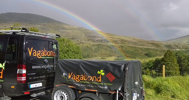 Tour vehicle parked with rainbow in the background