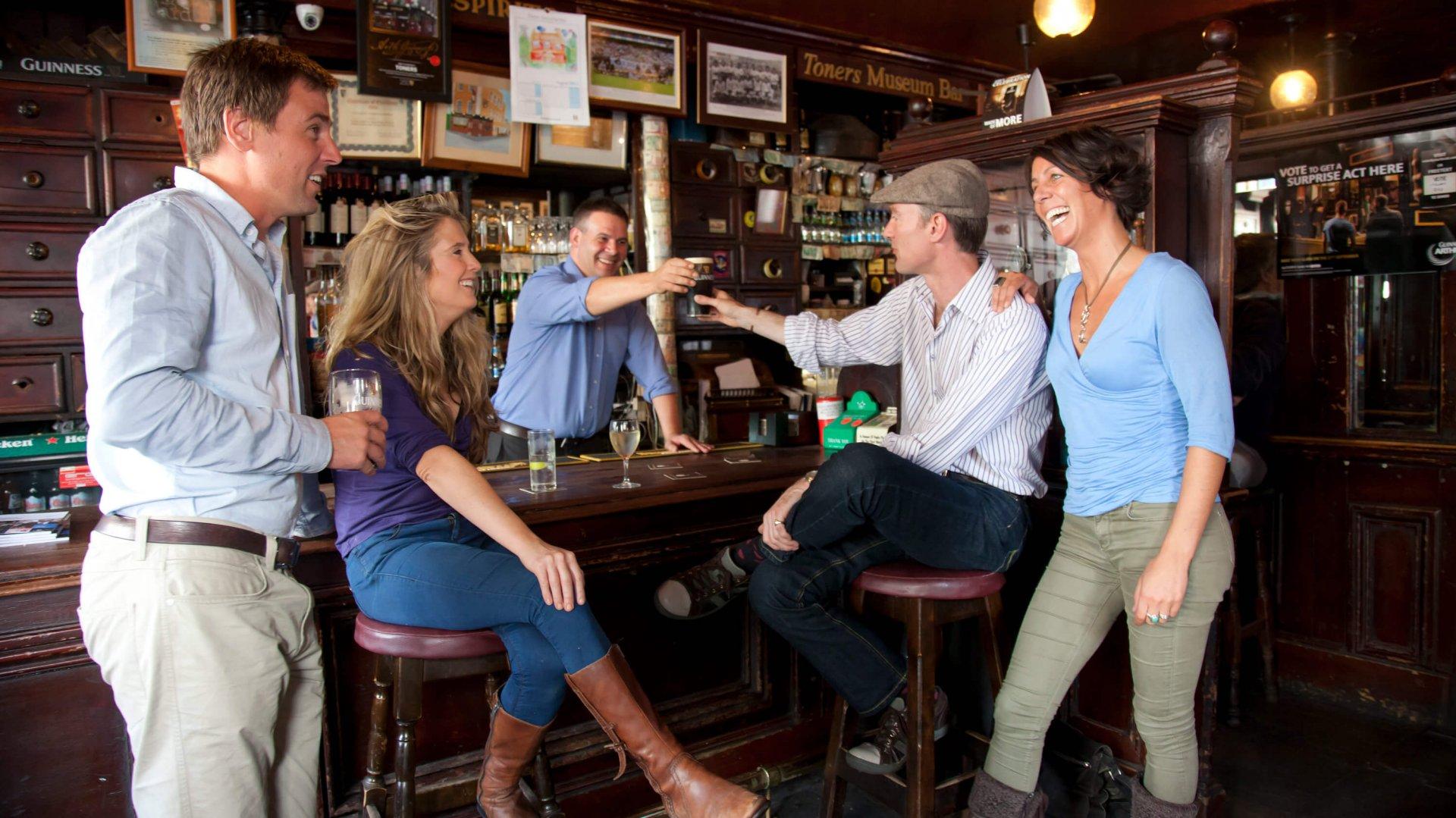 Group having fun with a barman in an Irish pub, saying cheers