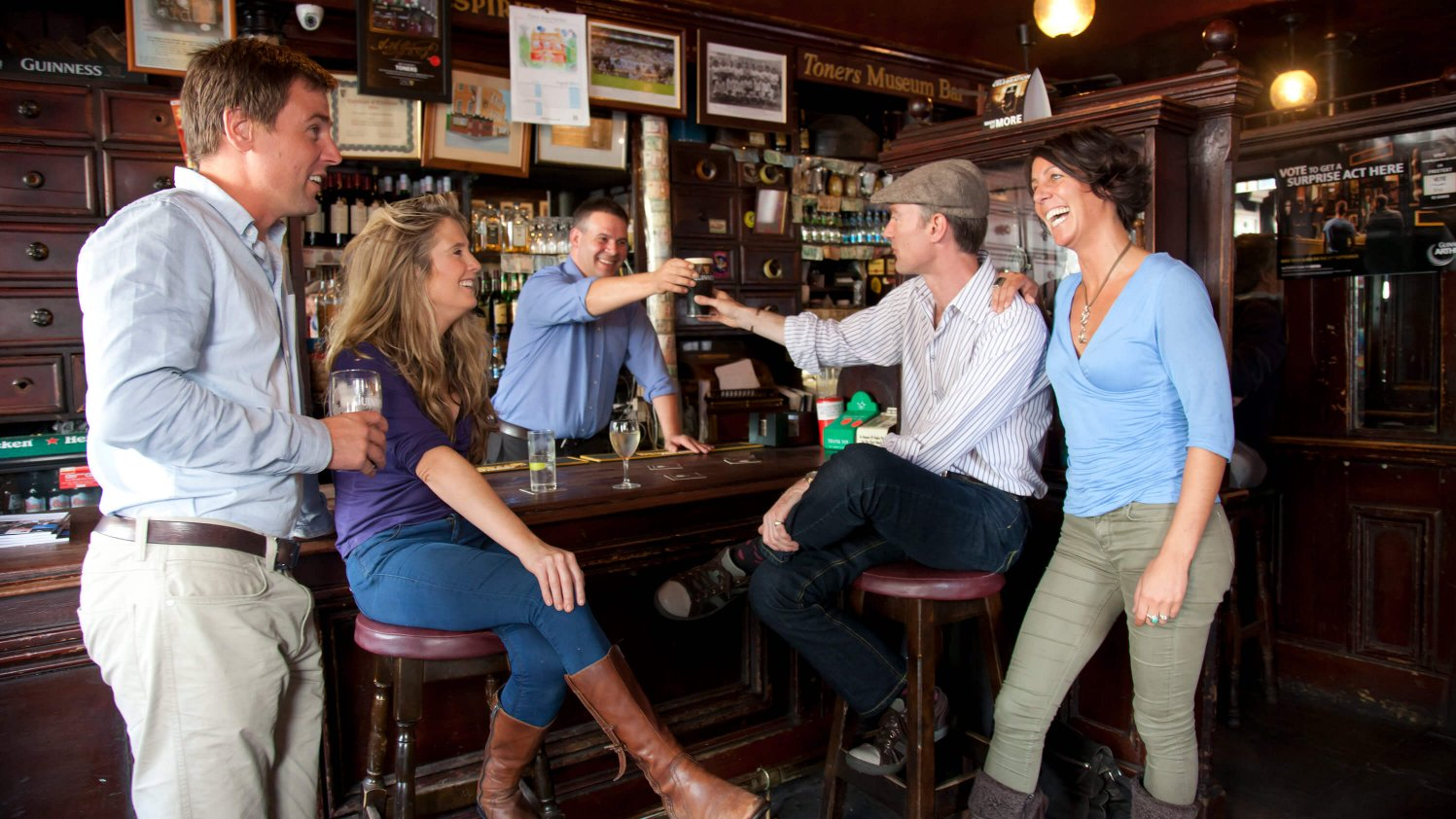 Group having fun with a barman in an Irish pub, saying cheers