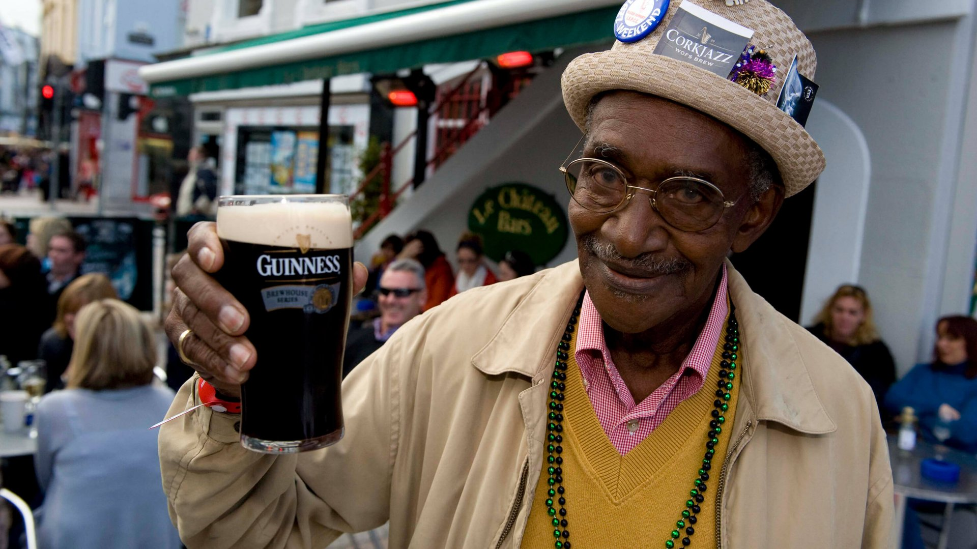 A happy man toasts the camera with a pint of Guinness