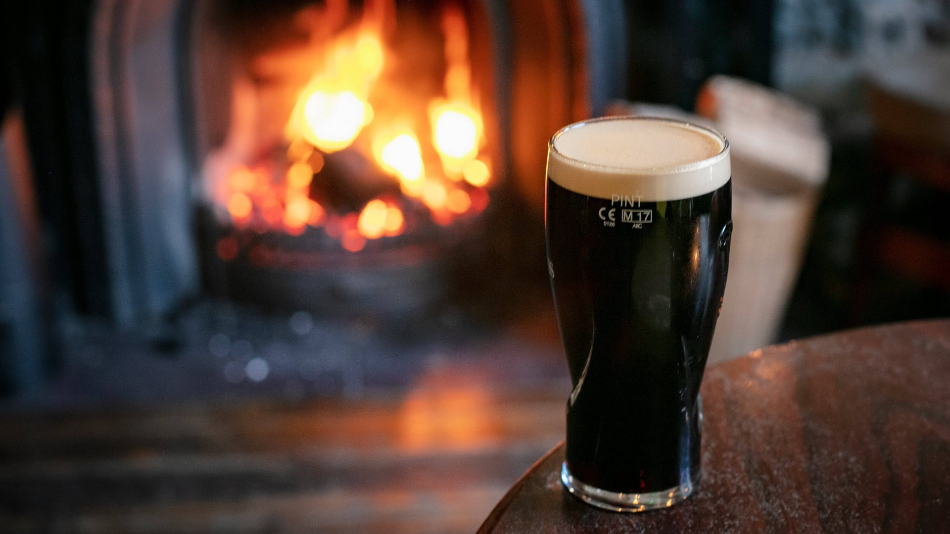 Pint of stout (probably Guinness or Murphy's) in front of a roaring fire in an Irish pub