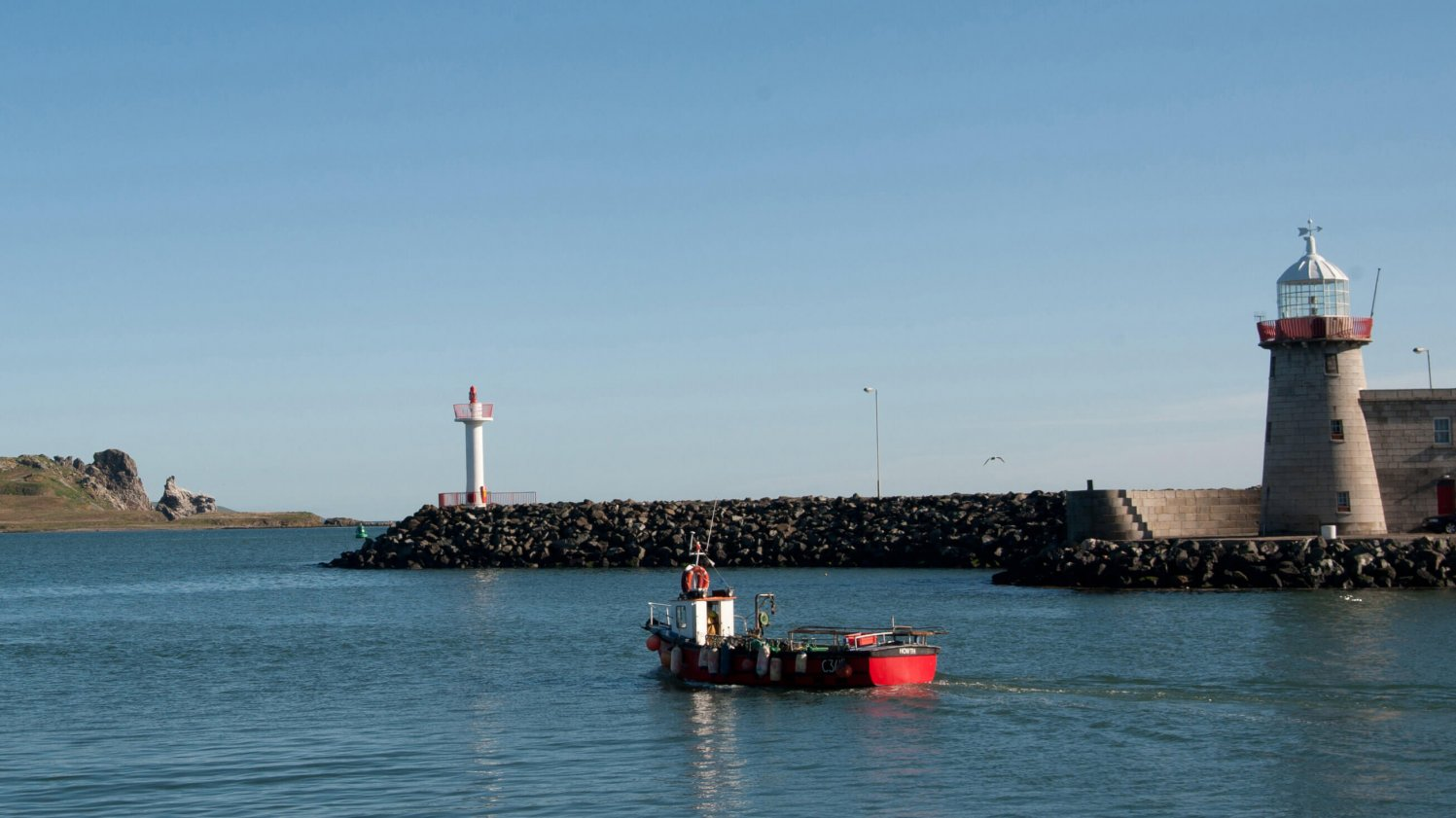 Boat and lighthouse in Howth harbour with Ireland's Eye in the background