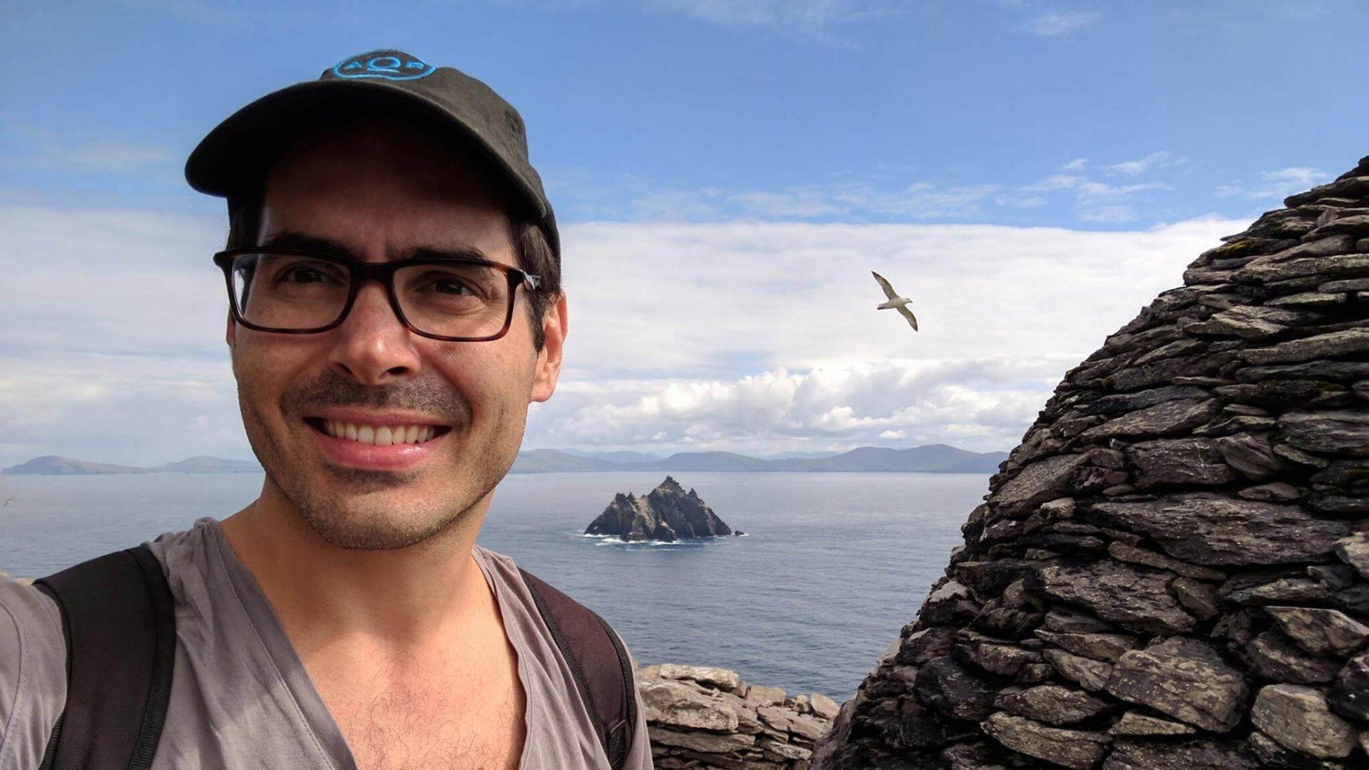 Vagabond guest Balint Pato takes a quick selfie (with passing seagull) at the beehive huts on top of Skellig Michael, with Little Skellig in the background