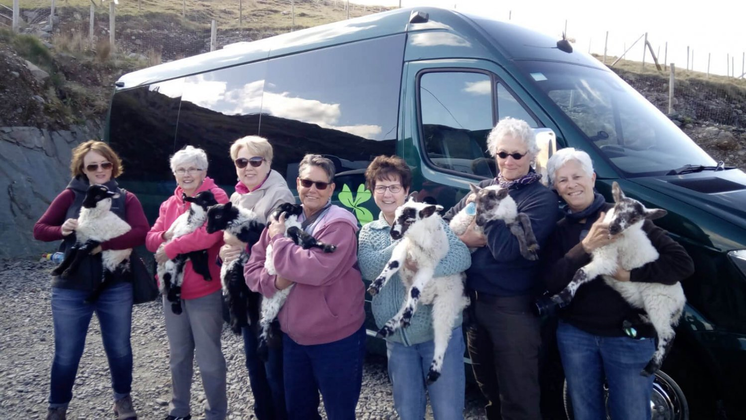 Group of Driftwood tour guests pose holding a baby lamb each