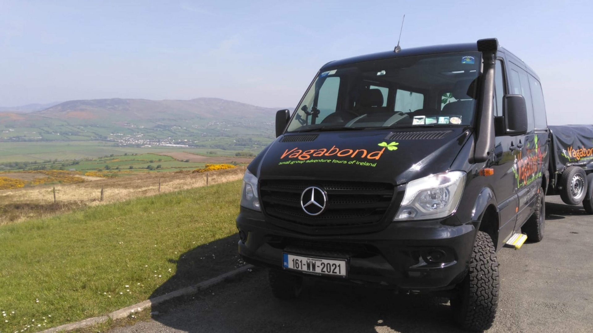 A 4x4 VagaTron touring vehicle parked up with blue skies and a lovely Irish landscape in the background