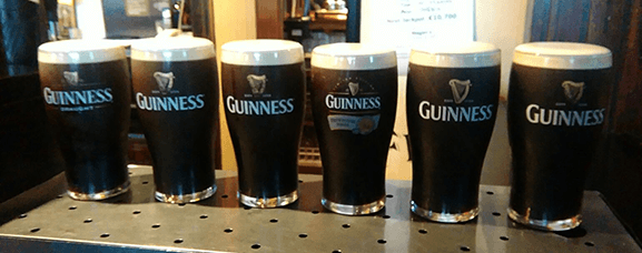 A line of Guinness pints