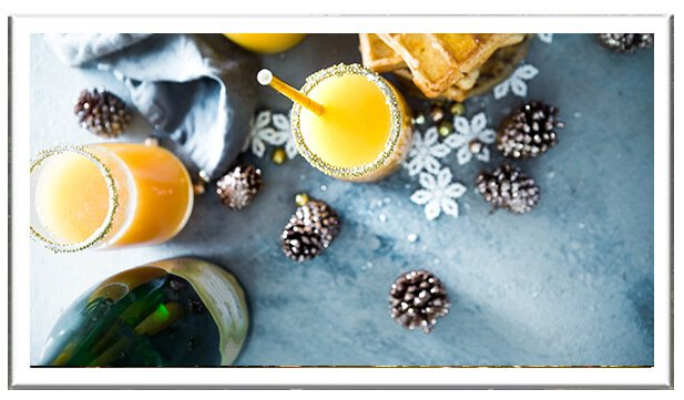 Festive bellini cocktails with decorative pine cones and bottle of sparkling wine