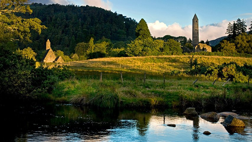 Tower and church near the river at Glendalough
