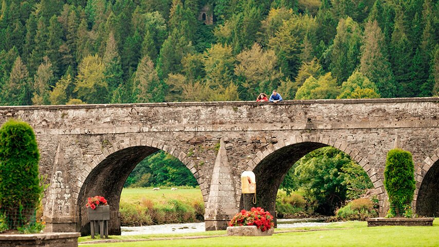 A couple gaze down from an arched bridge in Inistioge, Kilkenny