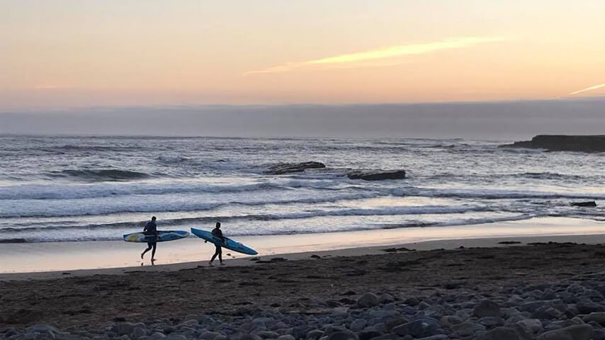 Surfers at sunset in Ireland