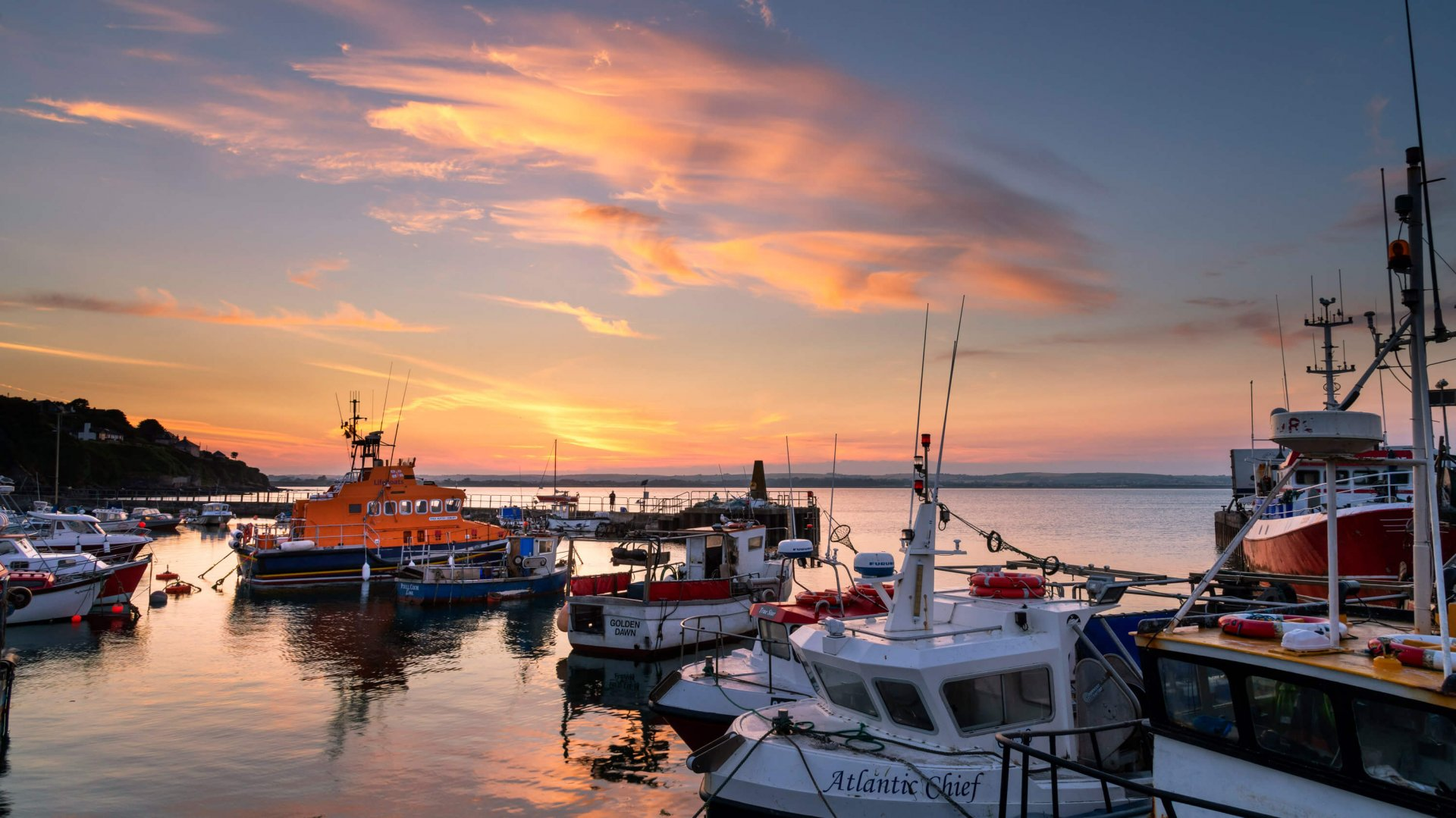 Ballycotton harbour at sunset with boats in the foreground, including a lifeboat