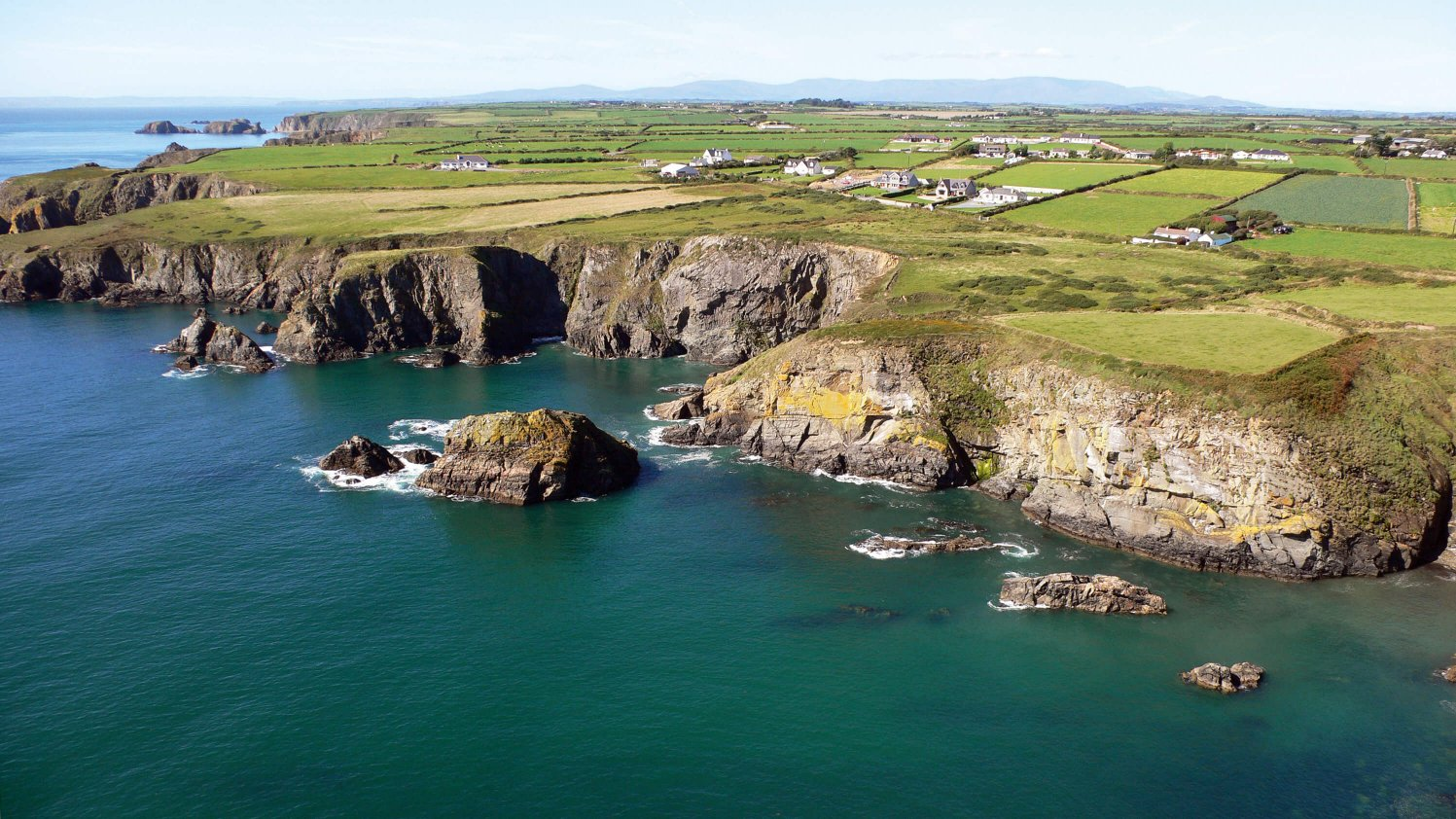 Sea, cliffs and patchwork green fields along the Copper Coast in Waterford