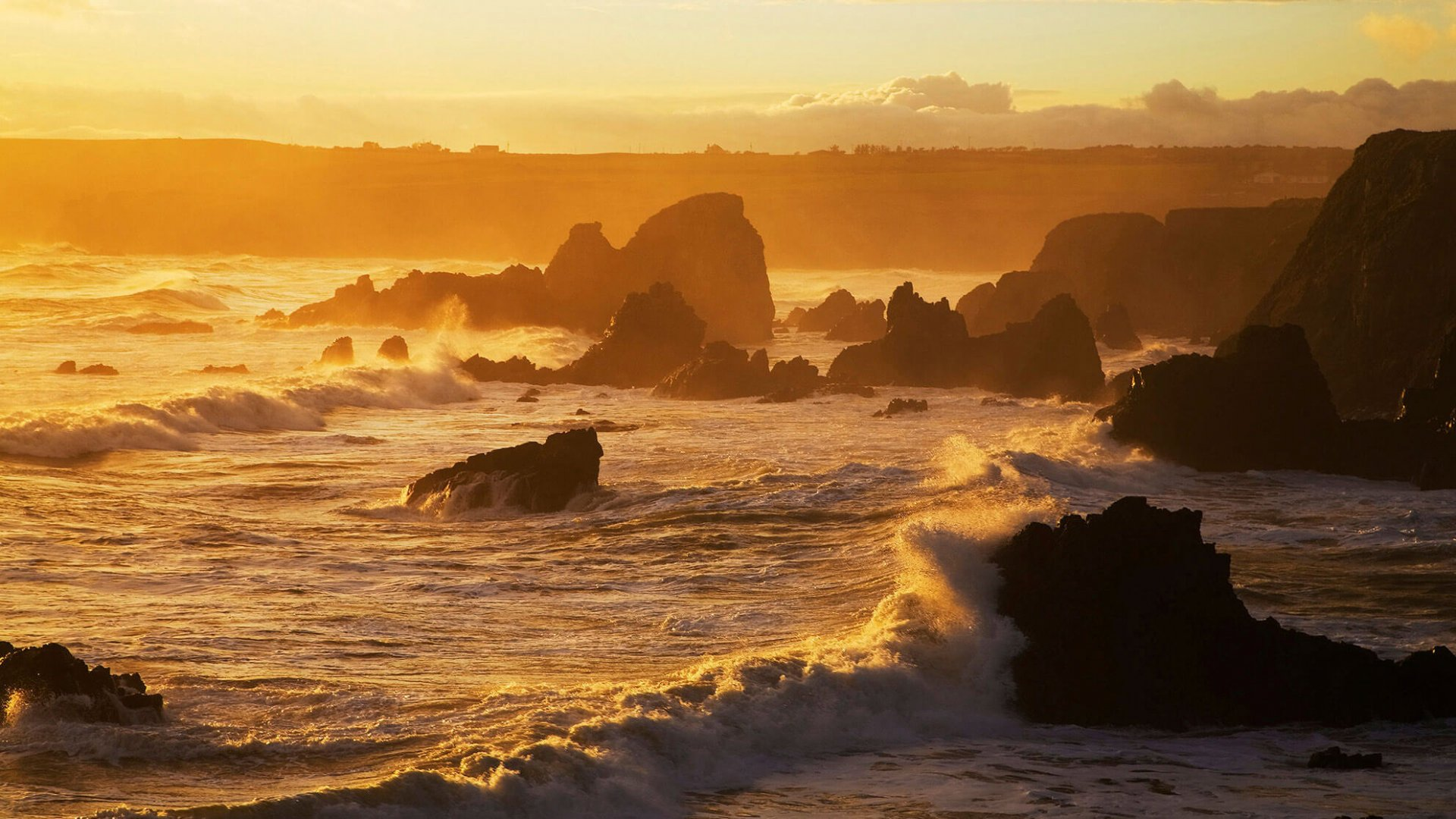 Evening light catches waves on Waterford's Copper Coast