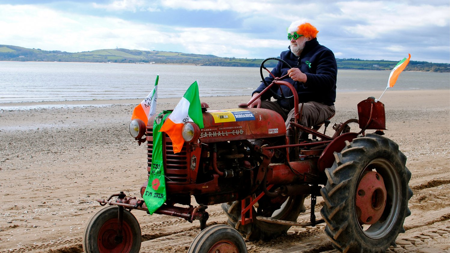 A stout man in a comedy wig and glasses driving a vintage tractor along a beach in Ireland