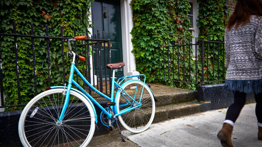 A vibrantly blue bike leans against the railing of an ivy-coloured Georgian front door as a female walks by