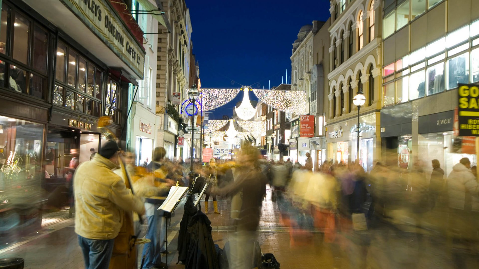 Hustle and bustle on Grafton Street at night including buskers
