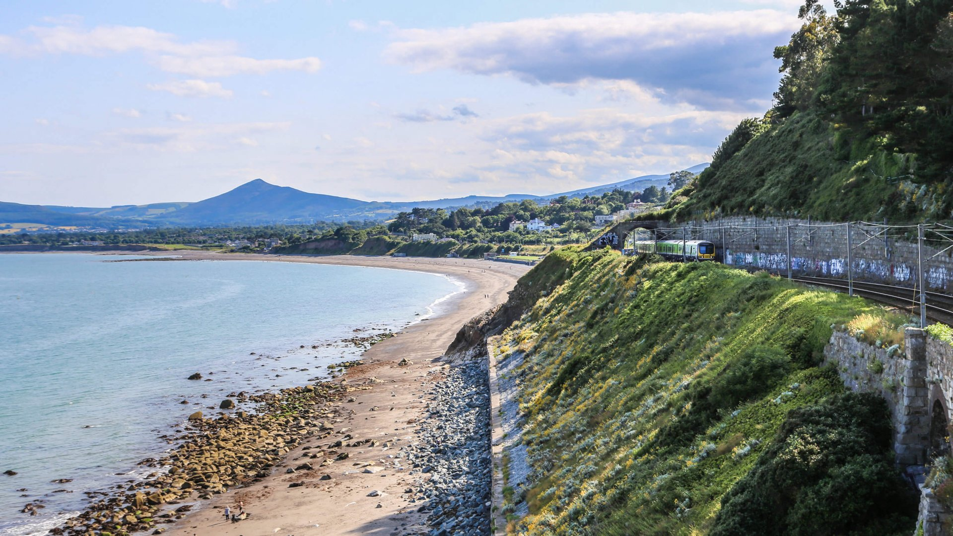 A DART train makes its way along Killiney Bay with the Sugarloaf mountain in the background