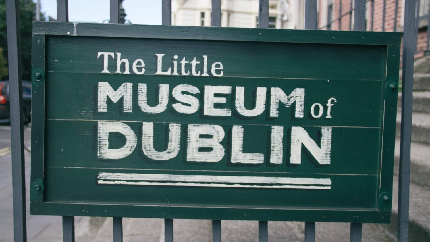 Green sign for Little Museum of Dublin hangs on a railing