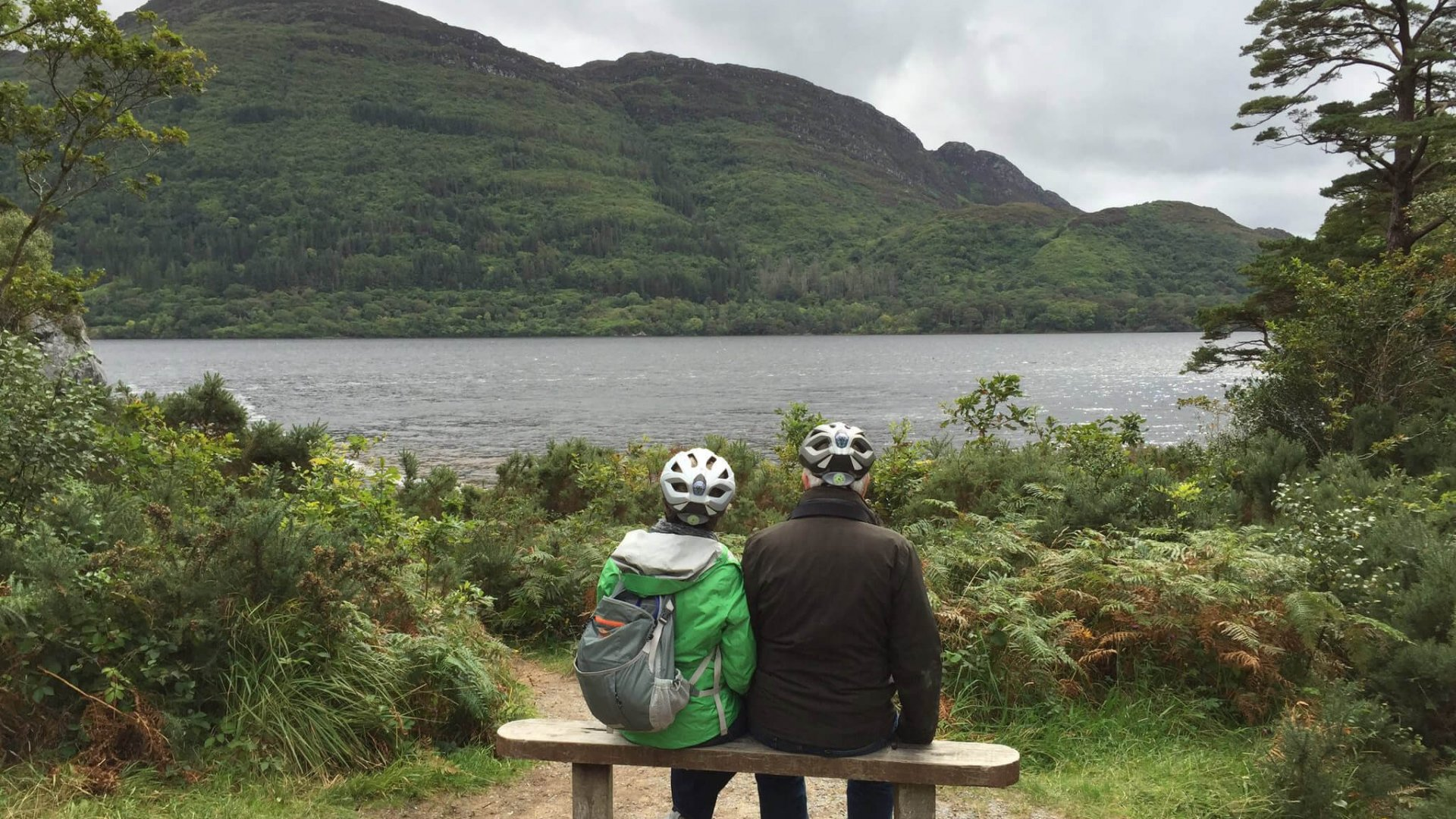 Couple dressed for cycling, sitting on a bench with their back to the camera, looking at the view of scenic Lough Leane in Killarney National Park, Ireland, on a Vagabond Tour